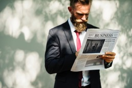 Guy holding newspaper with Business headline